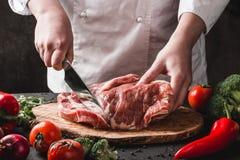 厨师屠户切口与刀子的猪肉在厨房,烹调食物 免版税库存图片