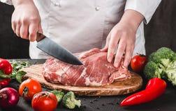 厨师屠户切口与刀子的猪肉在厨房,烹调食物 库存照片