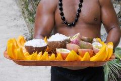 厨师岛民人供食在一个盘子的椰子和番木瓜果子在R 免版税库存图片