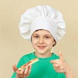 厨师帽子的小微笑的男孩尝试煮熟的薄饼 免版税库存图片