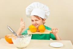 厨师帽子的小男孩与烹调了开胃松饼 免版税库存图片
