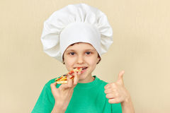 厨师帽子的小男孩品尝煮熟的薄饼 库存照片