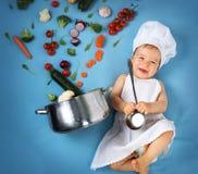厨师帽子的男婴有烹调的平底锅和菜 免版税图库摄影