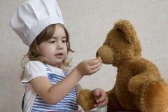 厨师帽子的画象可爱的小女孩 婴孩喂养一头玩具熊 免版税图库摄影