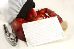 在厨师帽子的龙虾有食谱卡片的 免版税库存照片
