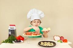 厨师帽子的年轻微笑的男孩在薄饼外壳上把一个搓碎干酪放 免版税库存图片