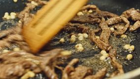 厨师平底锅油煎肉 人油煎在灼烧的煎锅的肉 在煎锅的火 关闭 肉烧烤  影视素材