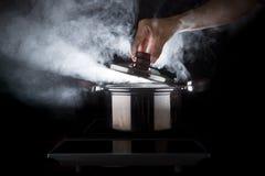 厨师开放热的小河罐的手有美好的演播室照明设备的 免版税图库摄影
