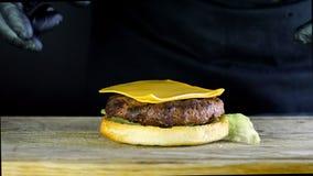 厨师形成与现成的成份的一个汉堡,炸肉排在小圆面包的一半说谎,并且两个切片乳酪是 影视素材