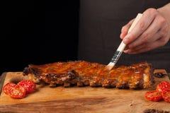 厨师得到在说谎在一张老木桌上的立即可食的猪排的BBQ调味汁 一个人准备一顿快餐对在a的啤酒 库存照片