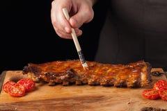 厨师得到在说谎在一张老木桌上的立即可食的猪排的BBQ调味汁 一个人准备一顿快餐对在一黑backgrou的啤酒 图库摄影