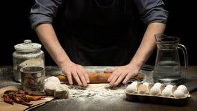 厨师手在木桌滚动面团 库存照片