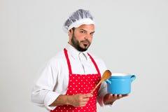 厨师拿着匙子和蓝色罐 免版税库存照片