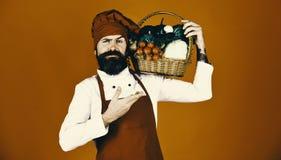 厨师拿着圆白菜、萝卜、硬花甘蓝用莴苣和大蒜 绿色杂货概念 有胡子的人在红色背景 库存照片