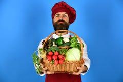 厨师拿着圆白菜、萝卜、硬花甘蓝用莴苣,胡椒和大蒜 免版税库存图片