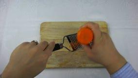 厨师摩擦在一台小磨丝器的红萝卜 影视素材