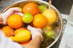 厨师柑橘水果的洗涤物混合在水槽的 免版税库存照片