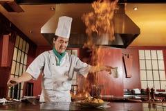 厨师油煎在厨房的菜 免版税库存照片