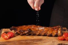 厨师洒在立即可食的猪排的盐,说谎在一张老木桌上 一个人准备一顿快餐对在一黑backgro的啤酒 免版税库存照片