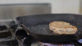 厨师烤在格栅的一块牛排 厨师烤肉 迷迭香和大蒜在肉 转动牛排 股票视频