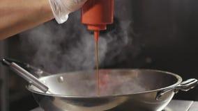 厨师特写镜头倒在油煎的食物的调味汁在铁锅平底锅,慢动作 股票视频