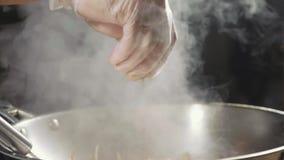 厨师特写镜头倾吐在油煎的食物的调味料在铁锅平底锅,慢动作 股票录像
