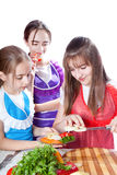 厨师的三个女孩准备一道蔬菜菜肴 免版税库存照片
