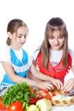 厨师的二个女孩准备一道蔬菜菜肴 图库摄影