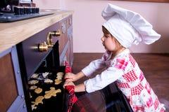 厨师的帽子的女孩在烤箱投入姜饼曲奇饼 免版税库存图片