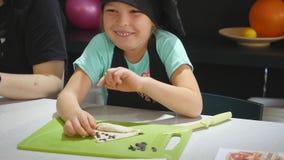 厨师的帽子的女孩在烹饪课期间的厨房里 影视素材