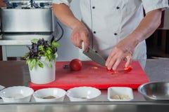 厨师的手切与一把刀子的一个蕃茄在厨房 免版税库存图片