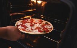 厨师的手在烤箱浸没比萨 免版税库存图片