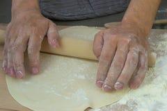 厨师的手揉在一张木桌上的面团 库存照片