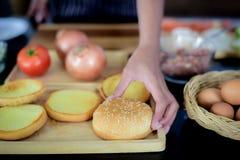 厨师的手采摘与芝麻的面包在上面 将被烘烤在做的火腿的一个平底锅,由成份围拢 免版税库存图片