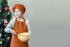 厨师的橙色帽子和围裙的一个逗人喜爱的男孩拿着烹调的一个杯子并且注视着狡猾地基督的背景 免版税库存照片
