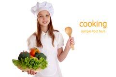 厨师的衣服的女孩有蔬菜和水果篮子的在被隔绝的背景 免版税库存照片