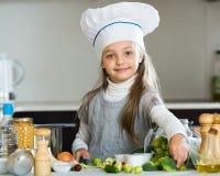 厨师盖帽的甜小女孩用新芽和硬花甘蓝 免版税库存照片