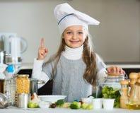 厨师盖帽的甜小女孩用新芽和硬花甘蓝 库存照片