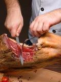 厨师砍了与一把被雕刻的长的刀子和别针的jamon在叉子 免版税库存图片