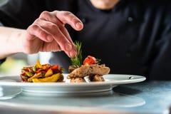 厨师精整和他准备的装饰食物 免版税库存照片