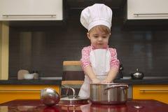 厨师衣服的小孩子帮助她的母亲在厨房里烹调 免版税库存图片