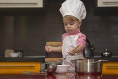厨师衣服的小孩子帮助她的母亲在厨房里烹调 免版税库存照片