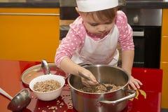 厨师衣服的小孩子帮助她的母亲在厨房里烹调 库存照片