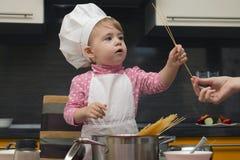 厨师衣服的小逗人喜爱的女孩在帮助她的母亲的厨房里烹调意粉 库存图片