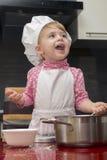 厨师衣服的Clouse-up画象微笑小逗人喜爱的女孩 母亲的帮手 两岁 免版税库存照片