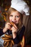 厨师衣裳的女孩用百吉卷在她手和微笑上 库存图片