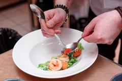 厨师装饰与三文鱼獐鹿的大虾开胃菜,被定调子 免版税库存照片