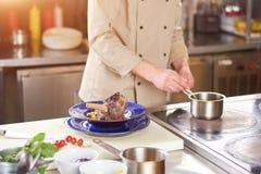 厨师调味汁为牛肉小腿做准备 免版税图库摄影