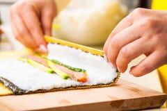 厨师转动nori板料与填装 免版税库存图片