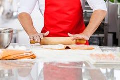 厨师辗压馄饨面团板料的中央部位在 免版税库存图片
